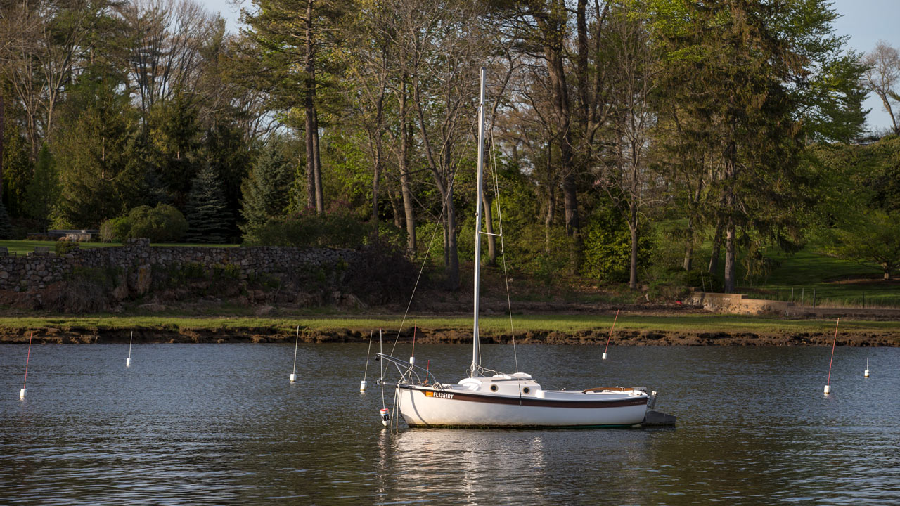 a single sailboat wih private lawn in background