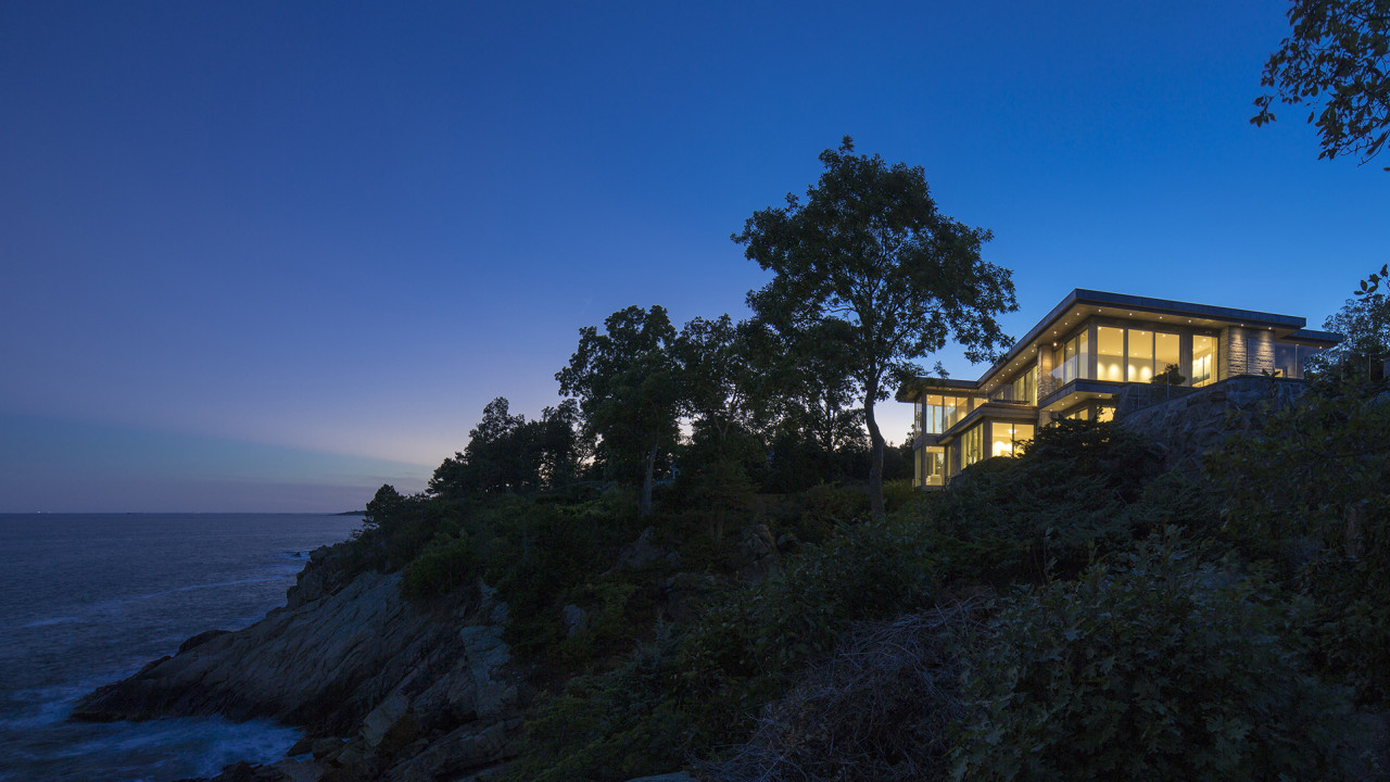 The oceanfront mansion lit from within, 65' above the water